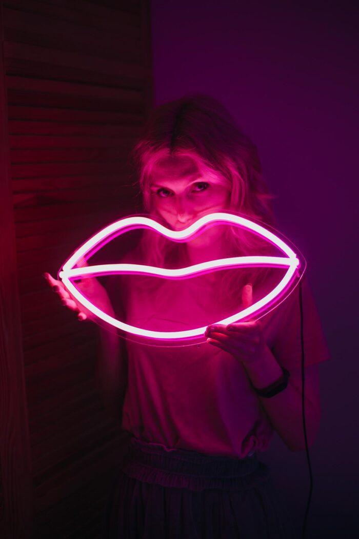Девушка, держащая розовую неоновую вывеску в виде губ