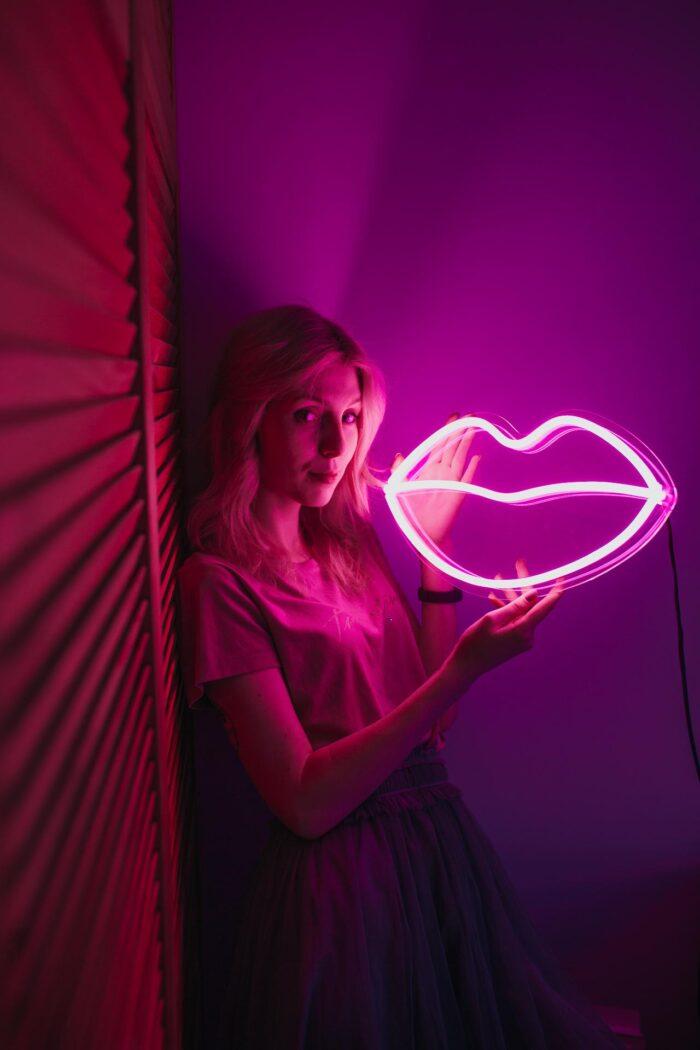 Девушка, держащая розовую неоновую вывеску в виде губ 1