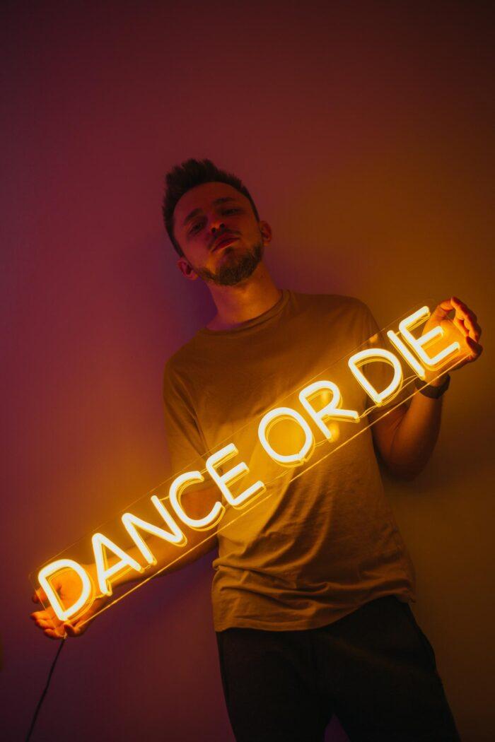 """Парень, держащий желтую неоновую надпись """"Dance or die"""" 3"""