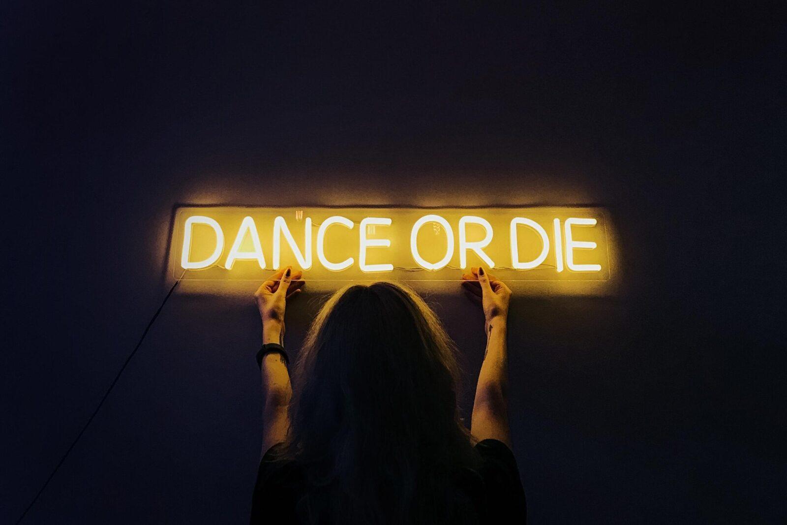 """Девушка, держащая желтую неоновую надпись """"Dance or die"""""""